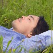 Young man lying on green grass — Stock Photo