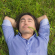 Young man lying on green grass — Foto de Stock