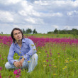 Stock Photo: Young man sitting in green meadow