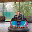 Senior man in small car at amusement park — Stock Photo