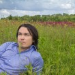 Young man lying on a spring meadow — Stockfoto