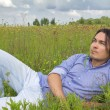 Man lying on a spring blossom meadow — Stock Photo