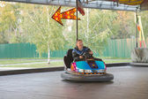 äldre man i liten bil på nöjespark — Stockfoto