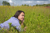 Young man lying on a spring meadow — Stock Photo