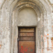Old arched abandoned door — Stock Photo