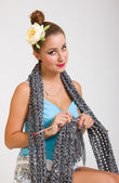 Young pinup woman knitting a scarf — Stock Photo