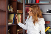 Serious girl in library looking for a book — Stock Photo