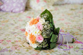 Wedding bouquet on bed — Stock Photo