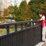 Young man walking on bridge — Stock Photo #35504641
