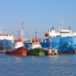 Cargo ships and guard boats docked in port — Stock Photo #7301035