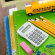 School supplies, pencils, toy school bus, note book, calculator — Stock Photo #51385773