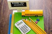 School supplies, pencils, toy school bus, note book, calculator — Stock Photo
