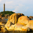 Lighthouse in early morning sunshine, sun shines on the rocks, Binh Thuan province, Vietnam — Stock Photo