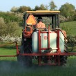 Farm tractor spraying field before planting — Stock Photo #12444420