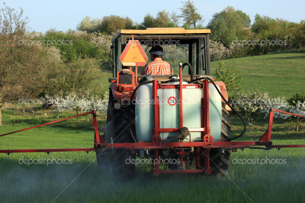 Tractor In Field Planting : Farm tractor spraying field before planting — stock photo