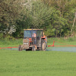 Farm tractor spraying field before planting — Stock Photo