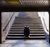 Lonely man sitting on the stairs — Stockfoto