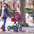 Young woman walking with her baby in the park — Stok fotoğraf