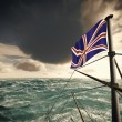 Union Jack over the waves - Stock Photo