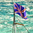 Union Jack waving over troubled waters - Stock Photo