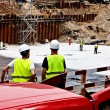 Construction workers discussing plans - Stock Photo