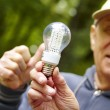 Senior mshowing eco diode bulb — Stock Photo #22441411