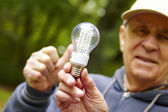 Senior man showing eco diode bulb — Stock Photo