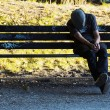 Homeless man sleeping on bench — Stock Photo