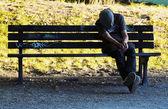 Homeless man sleeping on bench — Stock Photo