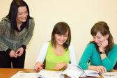 Mulheres jovens no exame final com professor — Fotografia Stock