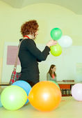 Happy female student playing with baloons — Stockfoto