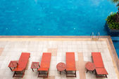 Poolside deckchairs alongside blue swimming pool — Stock Photo