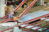 Construction worker grinding shopping mall's outdoor stairway st — Stock Photo