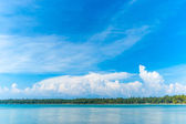 Beautiful cloudscape on vivid blue sky reflecting on the sea at — Stock Photo