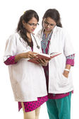 Two young Indian Female Doctors with notepad isolated on white. — Stock Photo