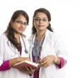 Two young Indian Female Doctors with notepad isolated on white. — Stock Photo #34927225