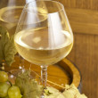 Glass of wine and grapes on wooden — Stock Photo #19747387