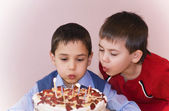 Boy blowing out candles on a chocolate birthday cake — Stock Photo