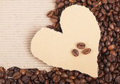 Coffee grains on paper the form of heart — Stock Photo
