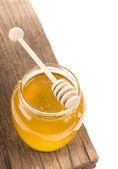 Honey in bank on wooden boards — Stock Photo