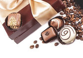 Brown box with candies and golden tape, coffee grains — Stock Photo