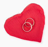 Big red heart from the fabric, two gold wedding rings — Stok fotoğraf