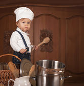 Boy in a cook cap among pans and vegetables — Stock Photo