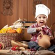 Royalty-Free Stock Photo: Boy in a cook cap among pans and vegetables