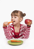 Cute little girl with the carrot and apple — Stock Photo