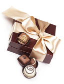 Brown box with candies and golden tape — Stock Photo