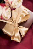 Bouquet of beautiful roses next to a gift — Stok fotoğraf