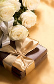Bouquet of beautiful roses next to a gift — Stock Photo