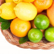 Fresh citrus fruit with leaves in a wicker basket — Stockfoto