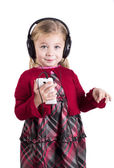 Little blonde girl smiling listening to music on smart phone mobile device — Stock Photo